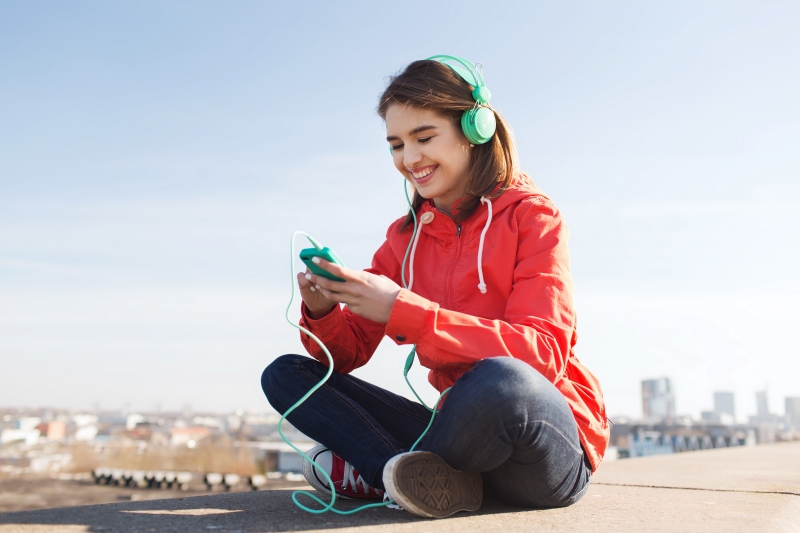 12205253-happy-young-woman-with-smartphone-and-headphones